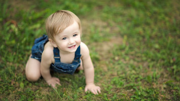 Happy, smiling Baby crawling around in Grass